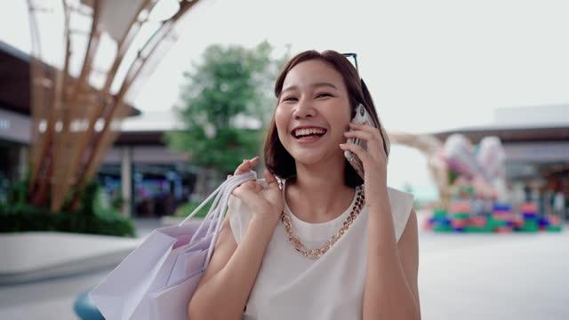 vídeos de stock e filmes b-roll de fashion people having fun in the community mall walking and holding her shopping bags - shopaholic