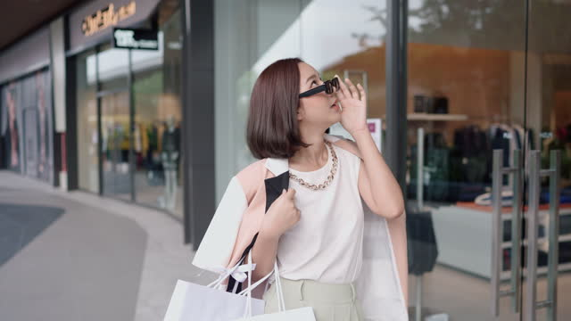 vidéos et rushes de les gens de mode ayant l'amusement dans le centre commercial de communauté marchant et retenant ses sacs à provisions - shopaholic