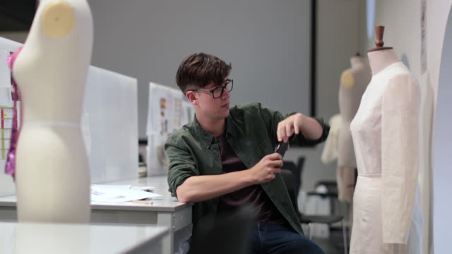 fashion student taking picture of a design with smartphone - トルソー点の映像素材/bロール