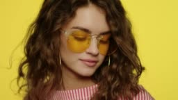 Fashion woman in sun glasses on yellow. Portrait of young woman dancing