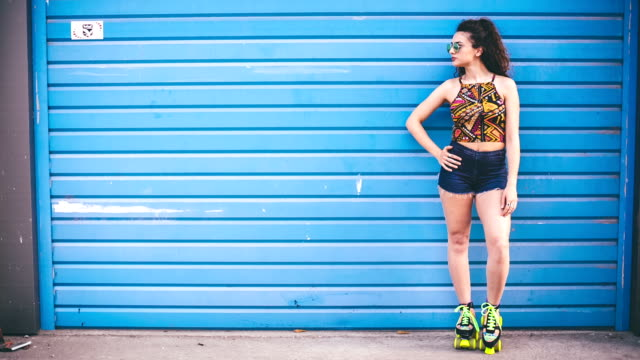 fashion woman with roller skates posing over blue background - shorts stock videos & royalty-free footage