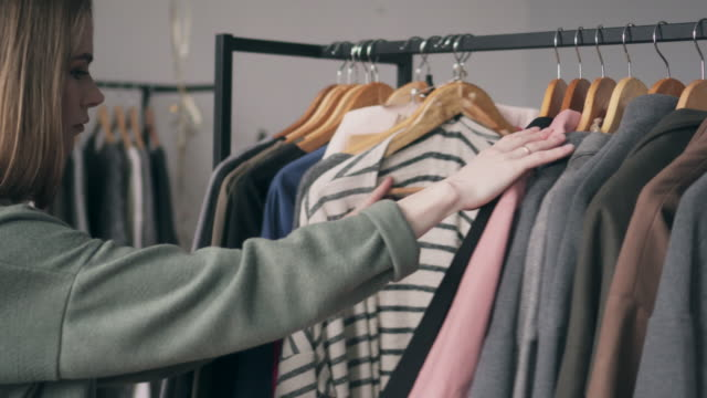 Fashion young woman choosing coat at clothing store