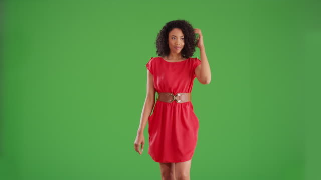fashionable black woman in red dress walking toward camera on green screen - model object stock videos & royalty-free footage