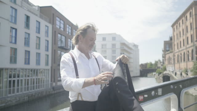 vidéos et rushes de fashionable businessman checks phone on bridge in london, close up - tenue habillée