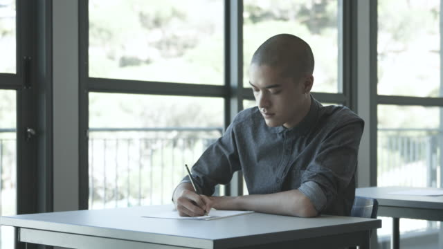 fashionable college student writes at table, medium shot - nose ring stock videos & royalty-free footage