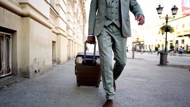 Fashionable entrepreneur with a suitcase walking in a city