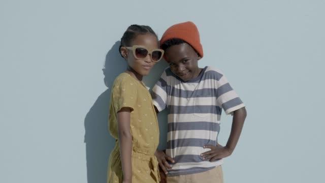 vídeos de stock e filmes b-roll de fashionable friends standing against blue background - fotografia de três quartos