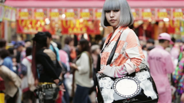 ms a fashionable girl poses in front of takeshita dori, harajuku district / tokyo, japan - fashion stock videos & royalty-free footage