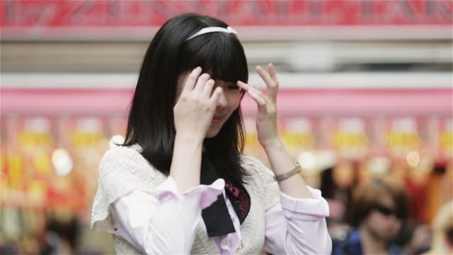 cu, tu a fashionable girl poses making the v or peace sign in front of takeshita dori, harajuku district / tokyo, japan - 美しい人点の映像素材/bロール