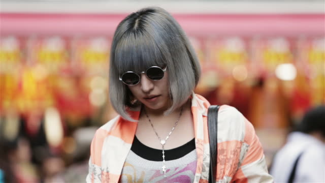 ms a fashionable girl puts on sunglasses and poses in front of takeshita dori, harajuku district / tokyo, japan - fashion stock videos & royalty-free footage