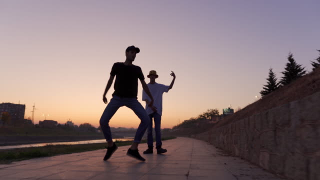 vidéos et rushes de hipsters à la mode dansant dans le coucher du soleil - breakdance