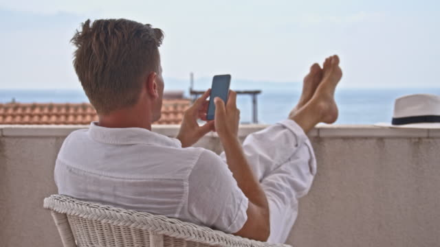 ds fashionable man using his phone on the balcony - balcony stock videos & royalty-free footage