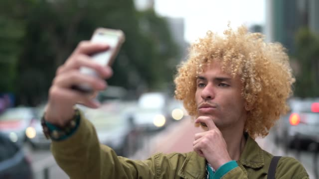 Fashionable Men with Curly Hair Taking a Selfie