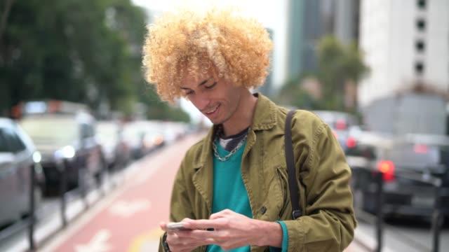 vídeos de stock, filmes e b-roll de homens na moda, com cabelos cacheados usando o celular na av. paulista, são paulo, brasil - cabelo encaracolado