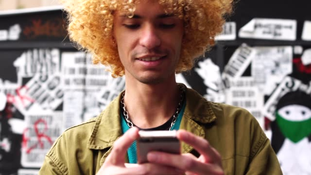 Fashionable Men with Curly Hair Using Mobile
