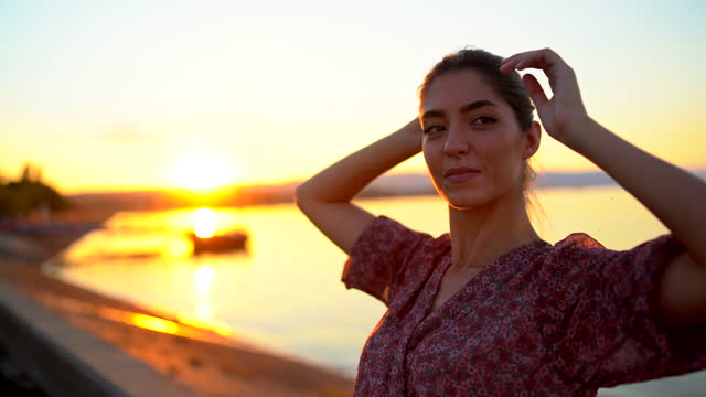 夕日にカメラのポーズをとっている美しい若い女性のファッショナブルなビデオ - 赤のドレス点の映像素材/bロール