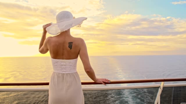 SLO MO Fashionable woman enjoying the sea travel at sunset