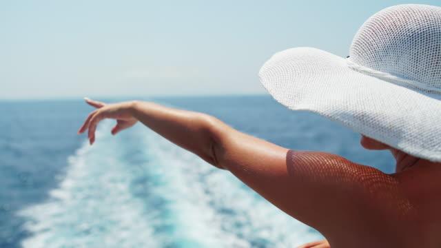 vidéos et rushes de la mode femme pointant à quelque chose de la terrasse - chapeau