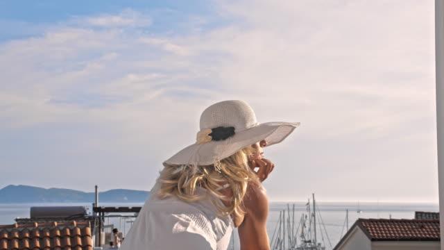 vídeos de stock e filmes b-roll de slo mo moda mulher relaxar na varanda - vestido branco