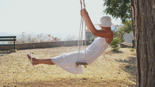vidéos et rushes de slo, dans le missouri, à la mode femme se balançant au bord de la mer - robe blanche