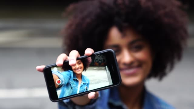 fashionable woman taking a selfie with curly hair at street - selfie video stock e b–roll