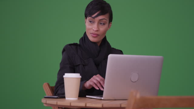 fashionable woman using laptop computer at a caf_ table on green screen - sitting stock videos & royalty-free footage