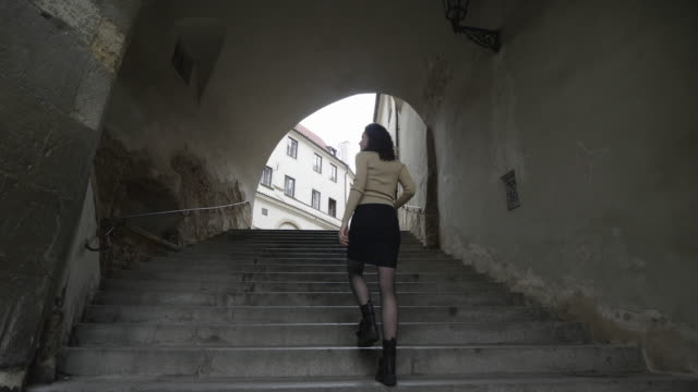 fashionable woman walks up old steps in prague, low angle - czech republic stock videos & royalty-free footage