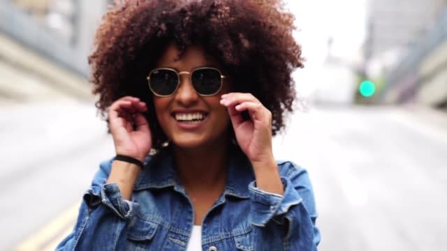 fashionable woman with curly hair at street - afro stock videos & royalty-free footage
