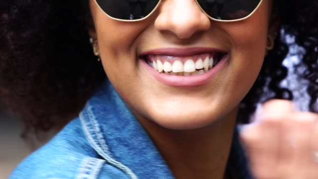fashionable woman with curly hair at street - sunglasses stock videos & royalty-free footage