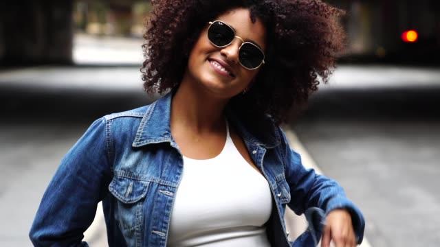 vídeos de stock, filmes e b-roll de moda mulher com cabelos cacheados na rua - cabelo encaracolado