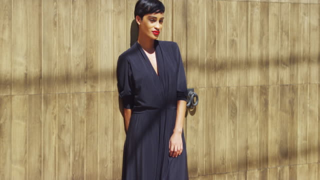 fashionable young black woman leaning against wall in sunlight - african american culture stock videos & royalty-free footage