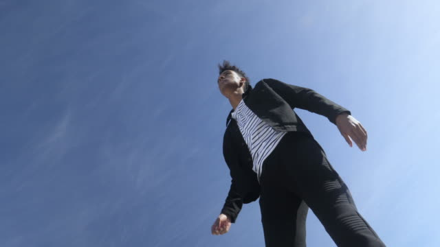 fashionable young man starts running against blue sky, low angle - fashionable stock videos & royalty-free footage