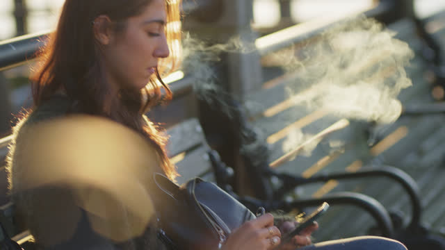fashionable young woman sits on bench by riverfront while using her phone and vaping - profile stock videos & royalty-free footage
