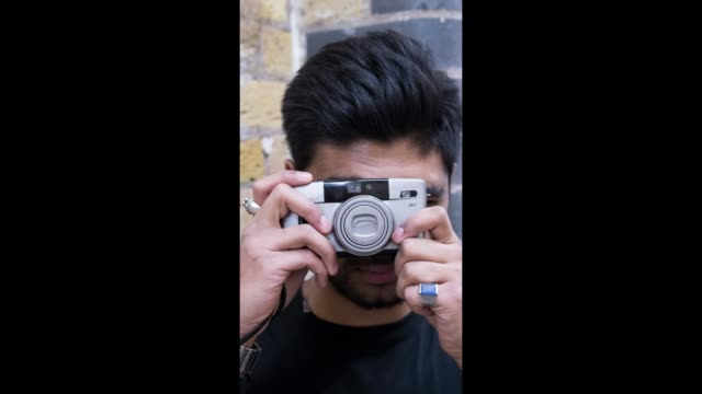 fashionista takes a picture on an old film camera during london fashion week men's on january 8, 2018 in london, england. - london fashion week点の映像素材/bロール