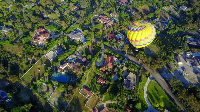 fast aerial above yellow hot air balloon - 熱気球点の映像素材/bロール