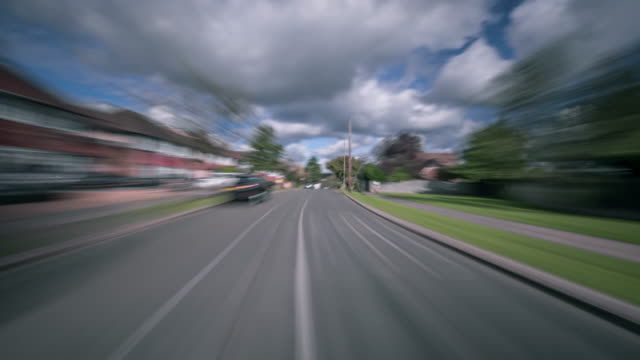 Fast blurred motion of a cars drivers POV traveling along the suburban streets North London passing homes and parked cars