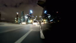 Fast city drive night road POV through city at night timelapse left side of car. Low angle view