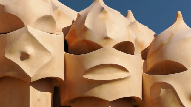 Fast motion close up face-like sculpture on La Pedrera roof/ zoom out wide shot sculpture with clouds passing behind/ Barcelona