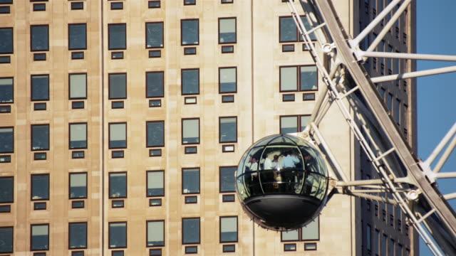 fast motion medium shot building exterior with millenium wheel capsules passing by/ london, england - ミレニアムホイール点の映像素材/bロール