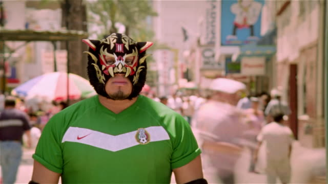 """fast motion medium shot luchador """"black tiger"""" standing in street with people passing by/ monterrey, mexico - nike designer label stock videos and b-roll footage"""