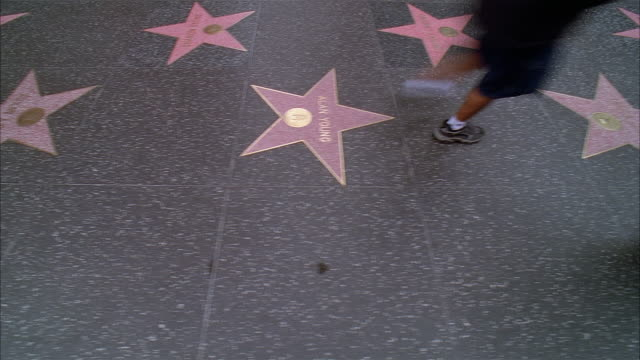 fast motion of pedestrians walking on hollywood walk of fame / hollywood, california - ウォークオブフェーム点の映像素材/bロール