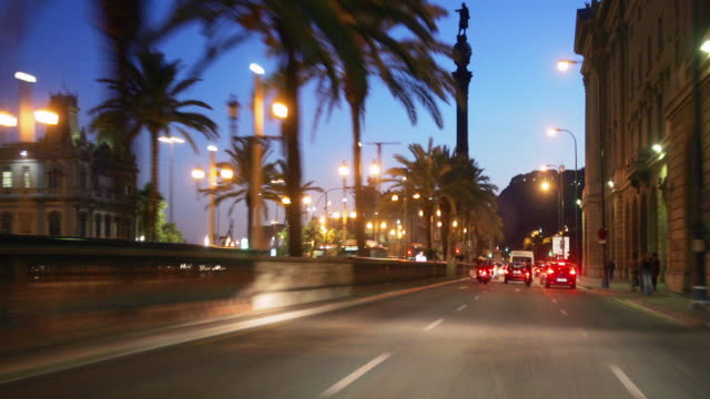 Fast motion wide shot driving point of view down Passeig de Colom at twilight/ Barcelona