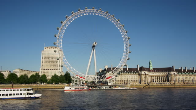 fast motion wide shot millenium wheel turning with boats passing by on thames/ london - circle stock videos & royalty-free footage