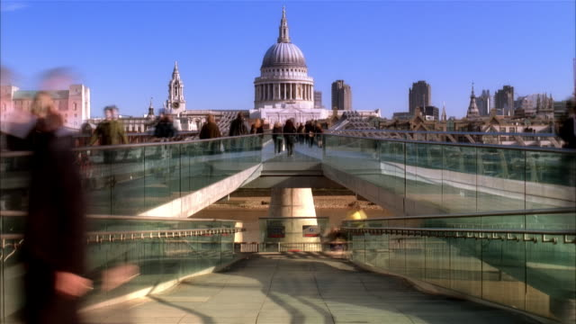 Fast motion wide shot pedestrians on Millenium Footbridge over Thames with view of St. Paul's Cathedral/ London
