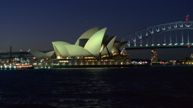 Fast motion wide shot Sydney Opera House and Sydney Harbour Bridge at night/