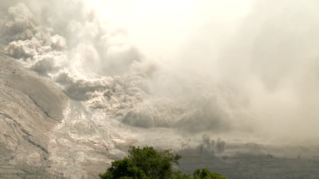 fast moving and dangerous pyroclastic flow sweeps down the side of sinabung volcano in sumatra indonesia on 19th june 2015 - pyroklastischer strom stock-videos und b-roll-filmmaterial
