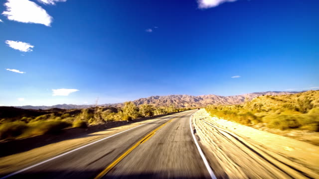 WS T/L POV Fast moving car on desert road hurdling towards mountains / Palm Springs, California, USA