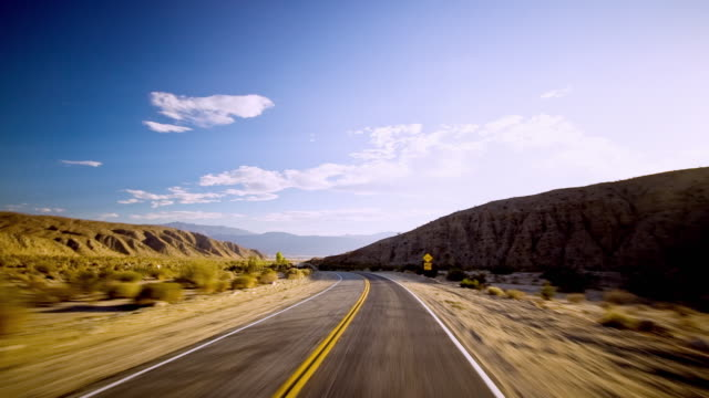 WS T/L POV Fast moving car travelling on winding mountain road and hurdling towards Coachella Valley / Palm Springs, California, USA