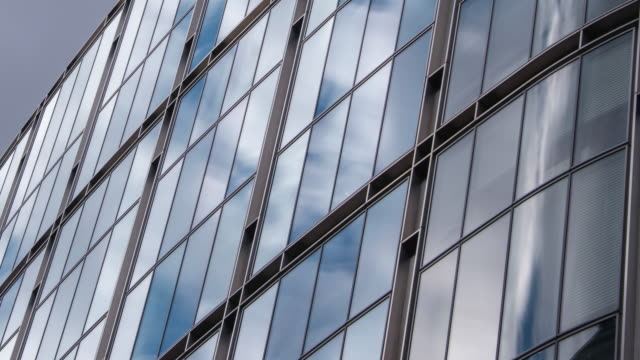 fast moving clouds and blue sky are reflected in a close-up of the glass and steel facade of a modern city office - jalousie stock-videos und b-roll-filmmaterial