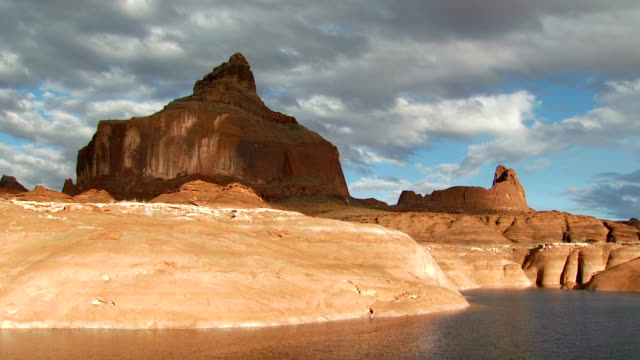 fast moving clouds over rock formation and water - lago powell video stock e b–roll